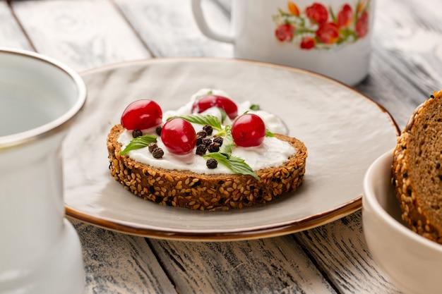 Torradas de pão com creme de leite e dogwoods em cinza Foto gratuita