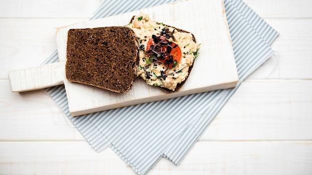 Torradas de pão com legumes macarrão e tomate na placa de madeira Foto gratuita