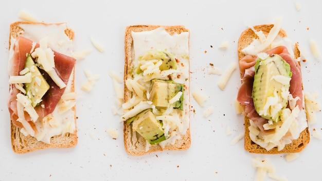 Torradas fatias de pão com queijo ralado; fatia de abacate e presunto em pano de fundo branco Foto gratuita