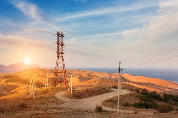 Torre de alta tensão nas montanhas ao pôr do sol Foto Premium