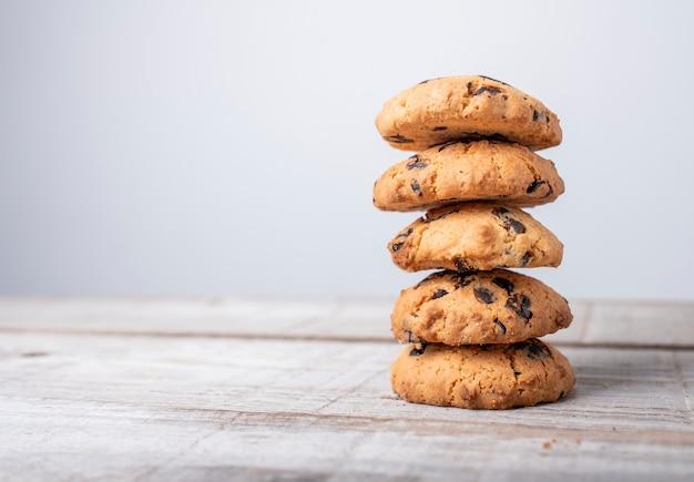 Torre de biscoito dourado com pedaços de chocolate no fundo de madeira Foto Premium