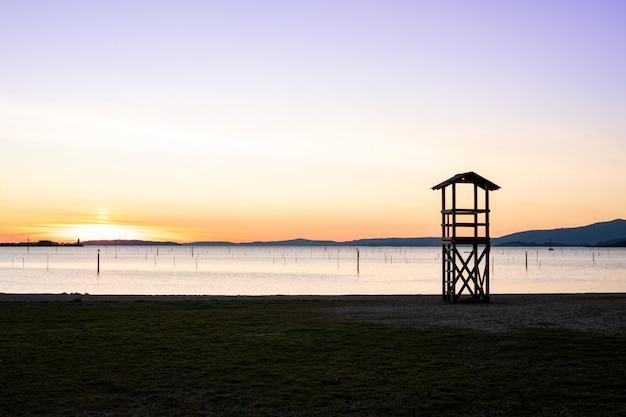 Torre de salvamento salva-vidas na praia ao pôr do sol Foto Premium