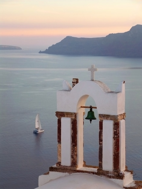 Torre de sino da igreja ortodoxa grega contra o mar egeu com barco à vela no pôr do sol, santorini, grécia Foto Premium