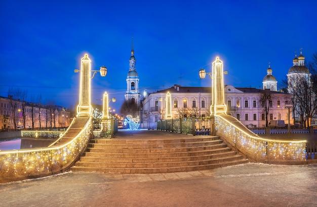 Torre do sino da catedral naval de são nicolau em são petersburgo e ponte krasnogvardeisky sob o céu azul noturno Foto Premium