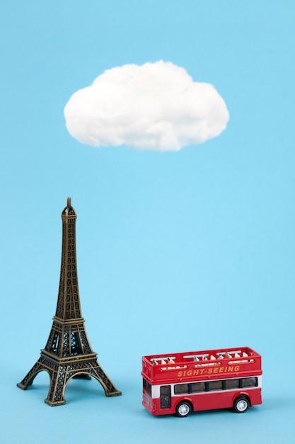 Torre eiffel em miniatura e ônibus turístico em fundo azul céu Foto Premium