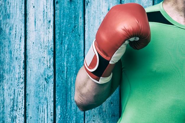 Torso de um homem e um homem da mão direita em luvas de boxe vermelhas Foto Premium