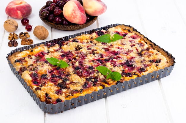 Torta caseira com frutas, frutas e nozes em forma de luz de fundo. Foto Premium