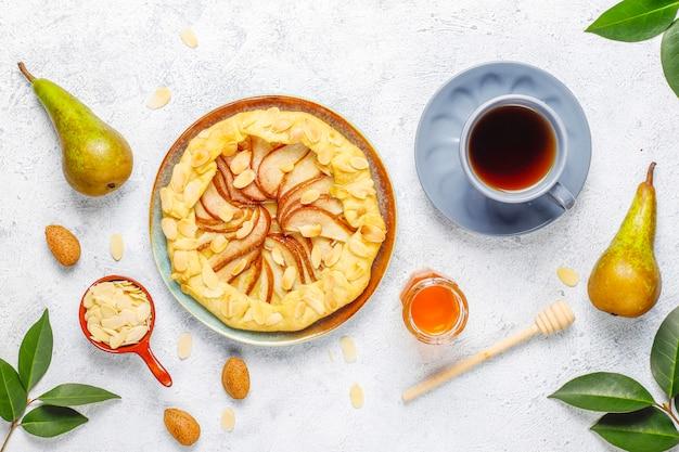 Torta caseira de galette de pera com folhas de amêndoa e peras verdes maduras frescas Foto gratuita