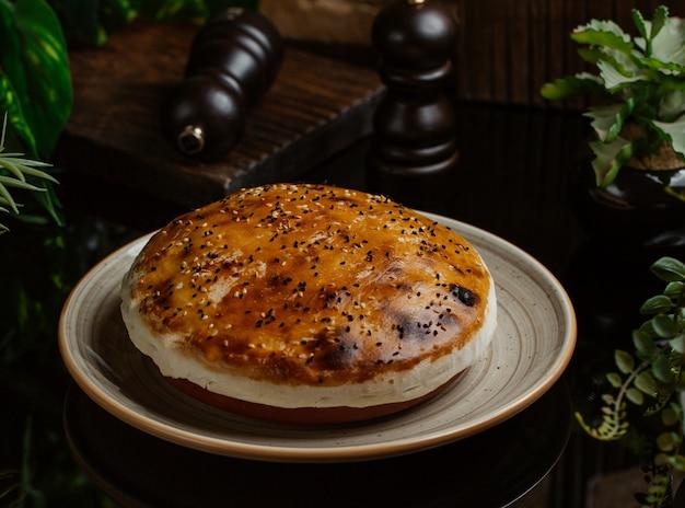 Torta de carne, redonda, coberta com gema de ovo e cozida finamente Foto gratuita
