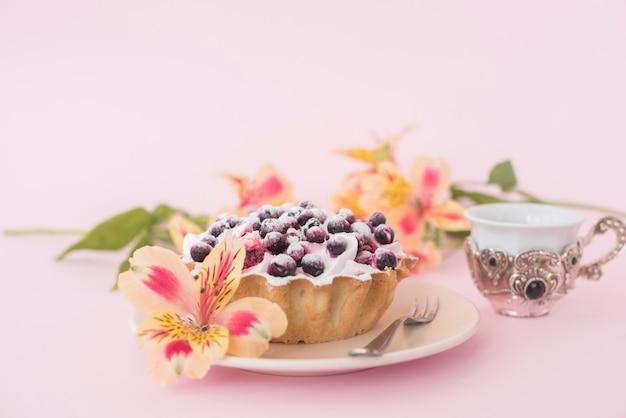 Torta de frutas servida na chapa branca com alstroemeria flor contra o pano de fundo-de-rosa Foto gratuita