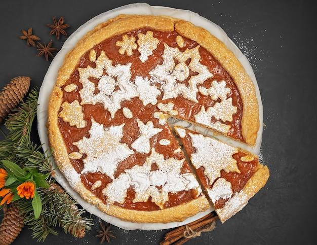 Torta de geleia caseira deliciosa de caqui. o bolo é decorado com figuras de natal de biscoitos. ao lado da torta são fatias de caqui e uma árvore de natal. vista do topo. Foto Premium