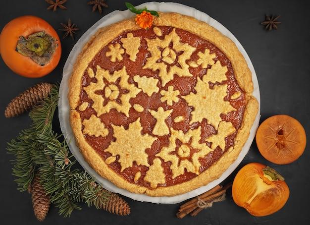 Torta de geleia caseira deliciosa de caqui. o bolo é decorado com figuras de natal de biscoitos. Foto Premium