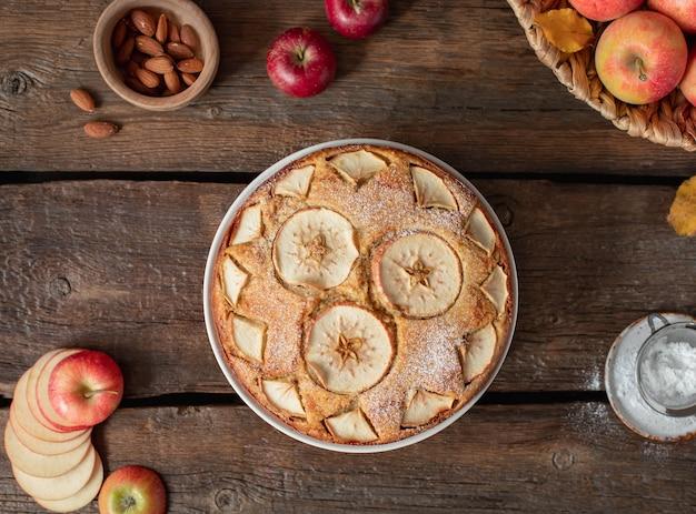 Torta de maçã em torno de maçãs, folhas, nozes em um rústico de madeira Foto Premium