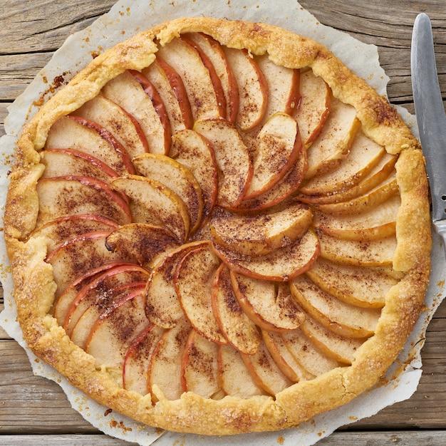 Torta de maçã, galette com frutas, bolos doces na mesa rústica de madeira velha Foto Premium