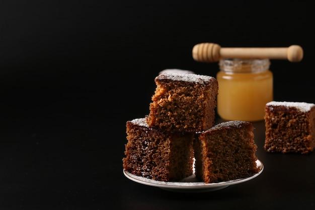 Torta de mel doce tradicional no feriado de ano novo judaico de rosh hashaná em um fundo escuro Foto Premium