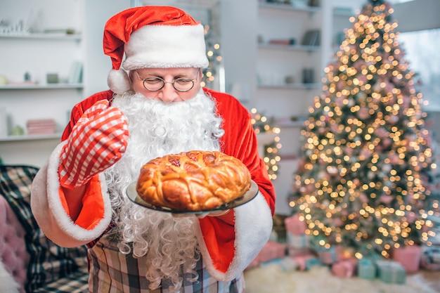Torta fresca e saborosa está nas mãos do papai noel. ele olha para ele e cheira. há uma árvore de natal atrás dele. Foto Premium