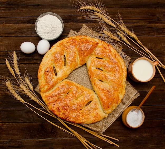 Torta, ingredientes para assar, espigas de trigo e caneca de leite. vista do topo Foto Premium