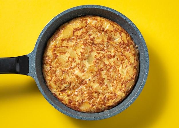 Tortilha de patatas no frigideira no prato espanhol amarelo, típico. Foto Premium