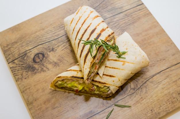 Tortilha fresca envolve com frango e legumes frescos na placa de madeira Foto Premium