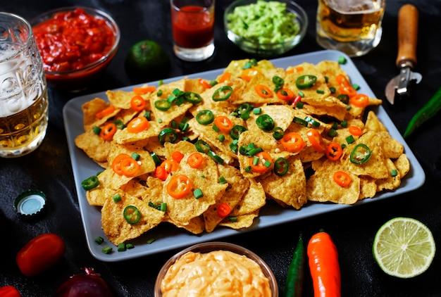 Tortilhas de tortilla de milho amarelo mexicano nachos com jalapeno, guacamole, molho de queijo e salsa Foto Premium