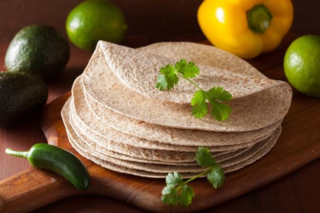 Tortilhas de trigo integral na placa de madeira e legumes Foto Premium