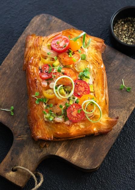 Tortinha de aperitivo caseiro de massa folhada com camarões, camarões, tomates, abacate, legumes e microgreens em fundo escuro. Foto Premium