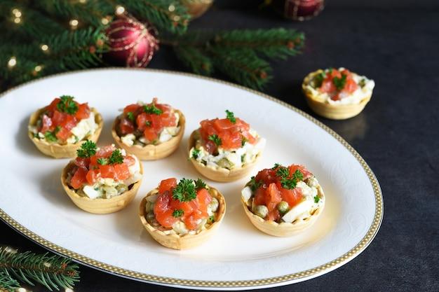 Tortinhas recheadas com salada e salmão em uma mesa de ano novo. mesa festiva com taça de champanhe Foto Premium