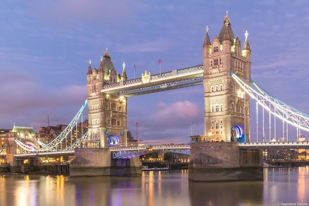 Tower bridge rodeada de edifícios e luzes à noite em londres, reino unido Foto gratuita