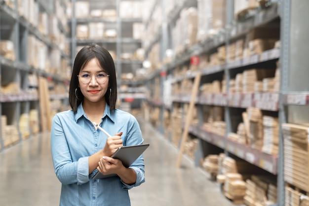 Trabalhador asiático atrativo novo, proprietário, mulher do empresário que guarda a tabuleta esperta que olha a câmera. Foto Premium