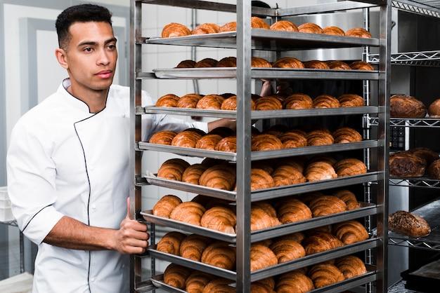 Trabalhador bonito de uniforme carregando prateleiras com croissant na padaria Foto gratuita
