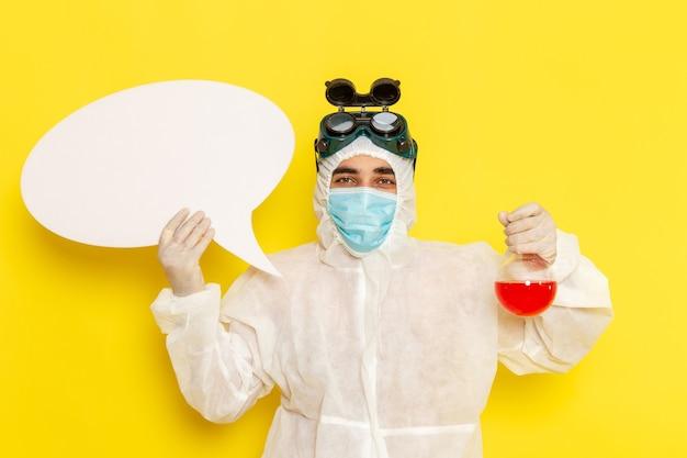 Trabalhador científico masculino de vista frontal em traje de proteção especial segurando o frasco com solução vermelha e placa branca na mesa amarela Foto gratuita