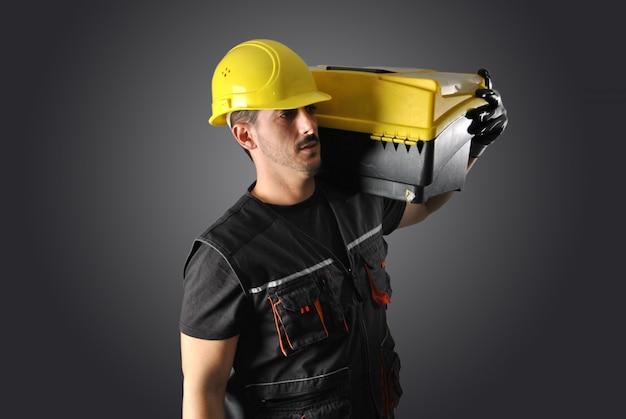 Trabalhador com capacete amarelo, broca e martelo Foto Premium