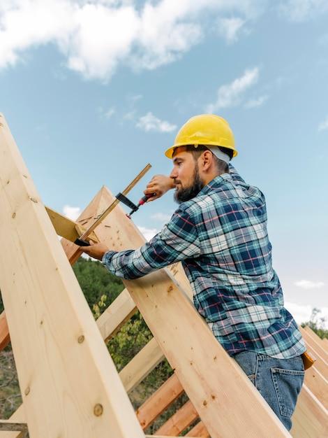 Trabalhador com capacete construindo o telhado da casa Foto gratuita