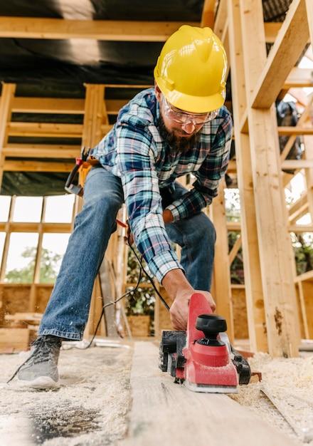 Trabalhador com capacete lixando pedaço de madeira Foto gratuita