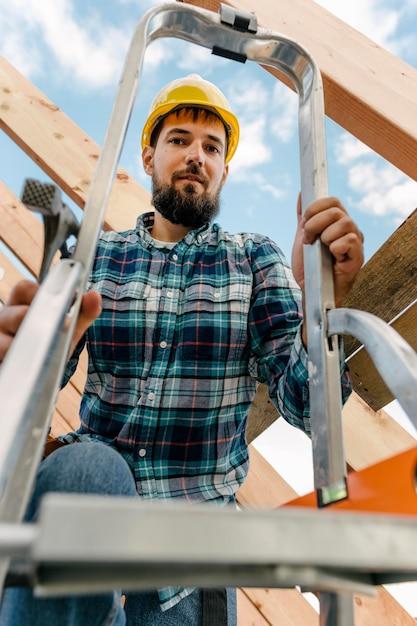 Trabalhador com capacete usando escada para construir o telhado da casa Foto gratuita