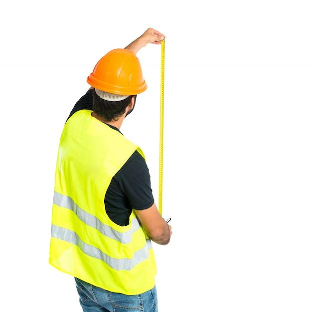 Trabalhador com medidor sobre fundo branco Foto gratuita