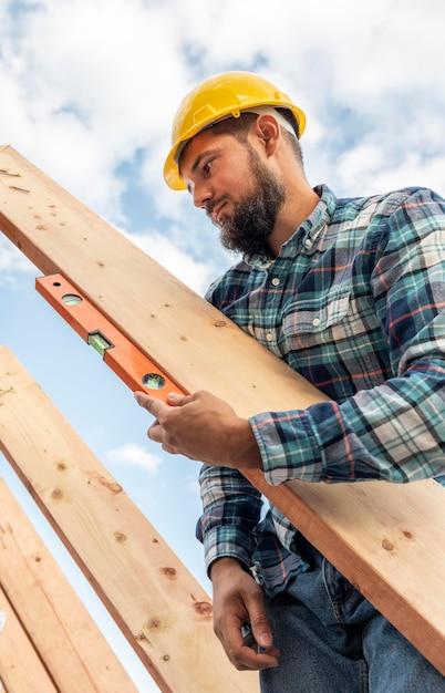 Trabalhador com verificação de nível da madeira do telhado Foto Premium