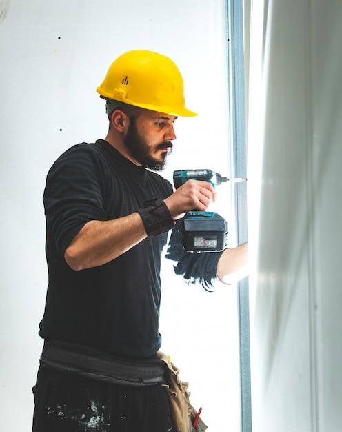 Trabalhador constrói uma parede de gesso cartonado. Foto Premium