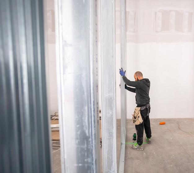 Trabalhador constrói uma parede de gesso cartonado Foto Premium