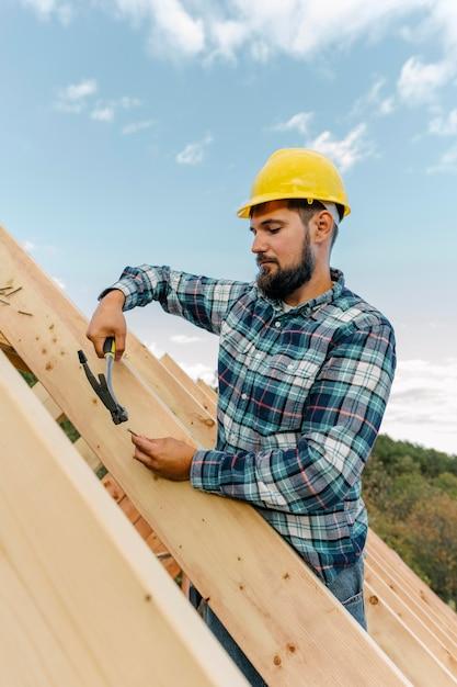 Trabalhador construindo o telhado da casa Foto gratuita