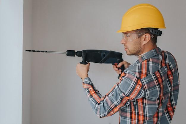 Trabalhador construtor com equipamento fazendo um buraco na parede no canteiro de obras Foto Premium