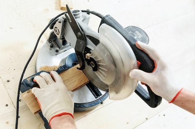 Trabalhador corta tábuas de madeira usando uma serra circular Foto Premium