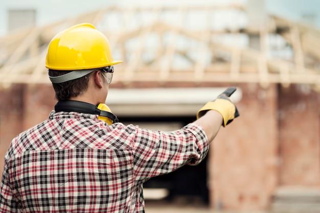 Trabalhador da construção civil apontando para algo Foto gratuita