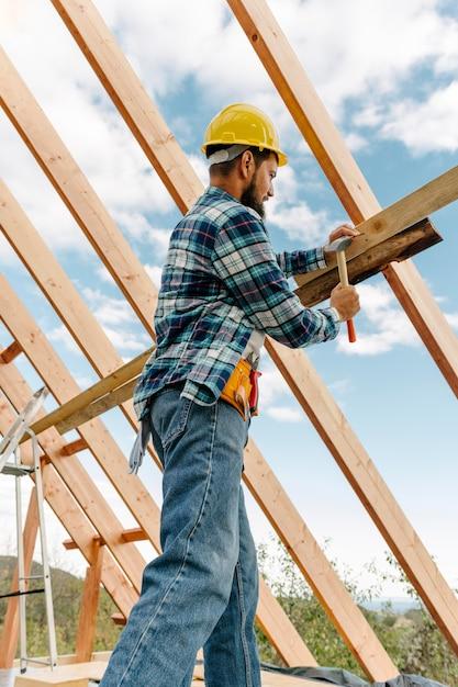 Trabalhador da construção civil com capacete construindo o telhado da casa Foto gratuita
