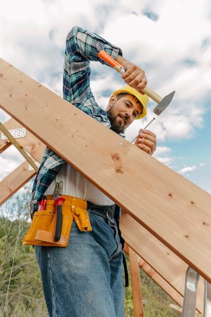 Trabalhador da construção civil com martelo construindo o telhado da casa Foto gratuita