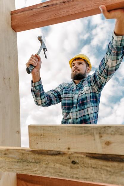 Trabalhador da construção civil com martelo e capacete construindo o telhado da casa Foto gratuita
