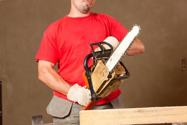 Trabalhador da construção civil com motosserra Foto Premium