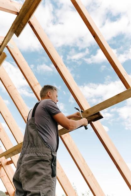 Trabalhador da construção civil construindo o telhado da casa Foto gratuita
