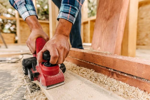 Trabalhador da construção civil lixando pedaço de madeira Foto gratuita