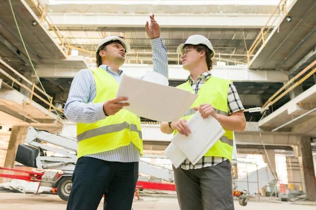 Trabalhador da construção civil masculino e engenheiro no canteiro de obras. Foto Premium